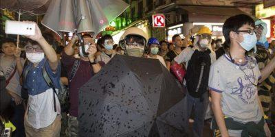 Manifestantes se protegen con paraguas del espray de pimienta utilizado por la policía en la calle Portland en el distrito de Mong Kok en Hong Kong (China) hoy. EFE