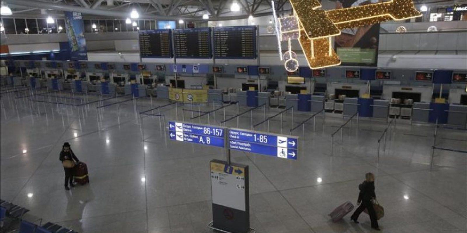 Dos viajeros atraviesan el vestíbulo vacío del aeropuerto Eleftherios Venizelos, que se ha sumado a la huelga general de 24 horas en Atenas (Grecia), hoy, jueves 27 de noviembre de 2014. EFE