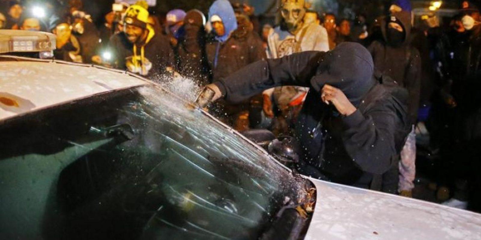 Un manifestante rompe la luna de un coche de policía ante el edificio del ayuntamiento en Ferguson (EE.UU.) durante unos disturbios provocados por la decisión de un gran jurado de no procesar al policía Darren Wilson por matar al joven Michael Brown en Ferguson, Misuri (Estados Unidos). EFE