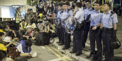 Activistas del movimiento pro-democracia de Hong Kong descansan en un parque, vigilados por una barrera policial. EFE