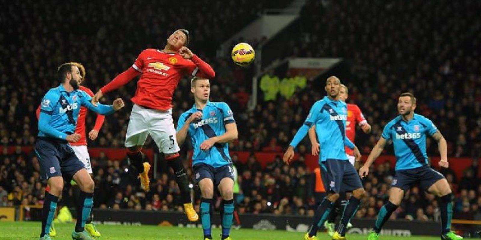 Marcos Rojo (2i) del Manchester United intenta cabecear ante el Stoke City con sus compañeros Chris Smalling (d) y Ashley Young (i) durante un partido de la Liga Premier inglesa en el estadio Old Trafford de Manchester (Reino Unido). EFE