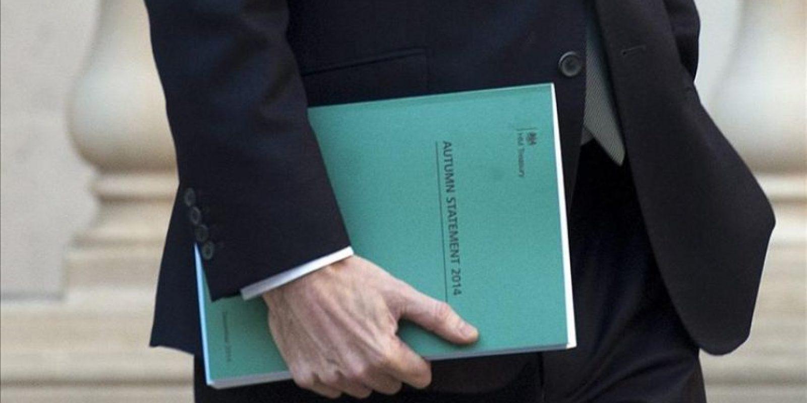 El ministro británico de Economía, George Osborne, sujeta una copia de la llamada Declaración de otoño mientras abandona la sede del Tesoro en Londres (Reino Unido), para dirigirse a la Cámara de los Comunes, hoy. Osborne ha presentado ante los diputados la llamada Declaración de otoño, en la que adelanta sus planes en cuanto a inversiones, recortes e impuestos para el Presupuesto del Estado, que se dará a conocer en marzo. El país celebrará sus elecciones generales en menos de seis meses. EFE