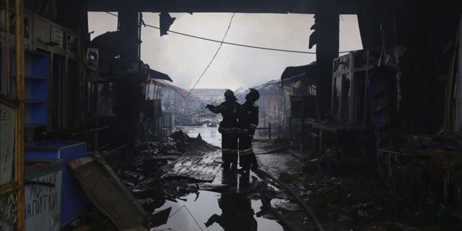 Dos bomberos inspeccionan los daños en un mercado que ardió tras un atentado terrorista en Grozni, la capital de Chechenia, en el Cáucaso. EFE