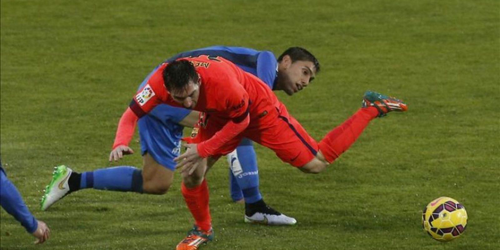 El delantero argentino del Barcelona Lionel Messi cae ante el defensa uruguayo del Getafe Emiliano Velázquez (detrás) en el partido de liga en Primera. EFE