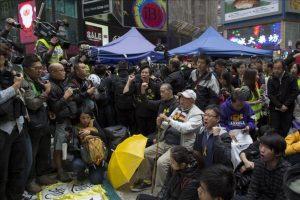 """El último grupo de manifestantes grita consignas mientras la policía desmantela el último campamento protesta de """"Occupy Central"""" en el distrito comercial honkonguense de Causeway Bay en China hoy, lunes 15 de diciembre de 2014. EFE"""