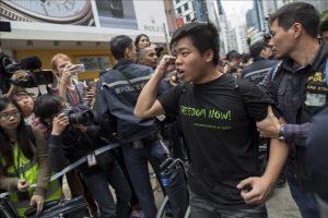 Un grita consignas mientras la policía lo detiene en el distrito comercial honkonguense de Causeway Bay en China hoy, lunes 15 de diciembre de 2014. EFE