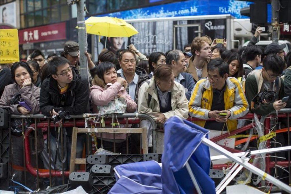 Varias personas observa cómo la policía desaloja las barricadas de los manifestantes en el distrito comercial honkonguense de Causeway Bay en China hoy, lunes 15 de diciembre de 2014. EFE