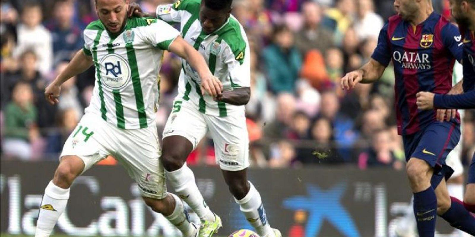 El defensa del FC Barcelona Javier Alejandro Mascherano (d) y el los jugadores del Córdoba, el argelino Nabil Ghilas y el camerunés Patrick Ekeng (c) durante el partido correspondiente a la decimosexta jornada de Liga. EFE