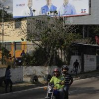 Salvadoreños pasan frente a una valla publicitaria de candidatos de la opositora Alianza Republicana Nacionalista (ARENA), hoy miércoles 31 de diciembre de 2014 por las principales calles de San Salvador (El Salvador). EFE