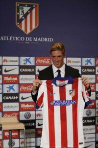 El delantero Fernando Torres muestra la camiseta que lucirá con el Atlético de Madrid durante su presentación como nuevo jugador rojiblanco, en su regreso cedido hasta el 30 de junio de 2016, esta mañana en el estadio Vicente Calderón. EFE