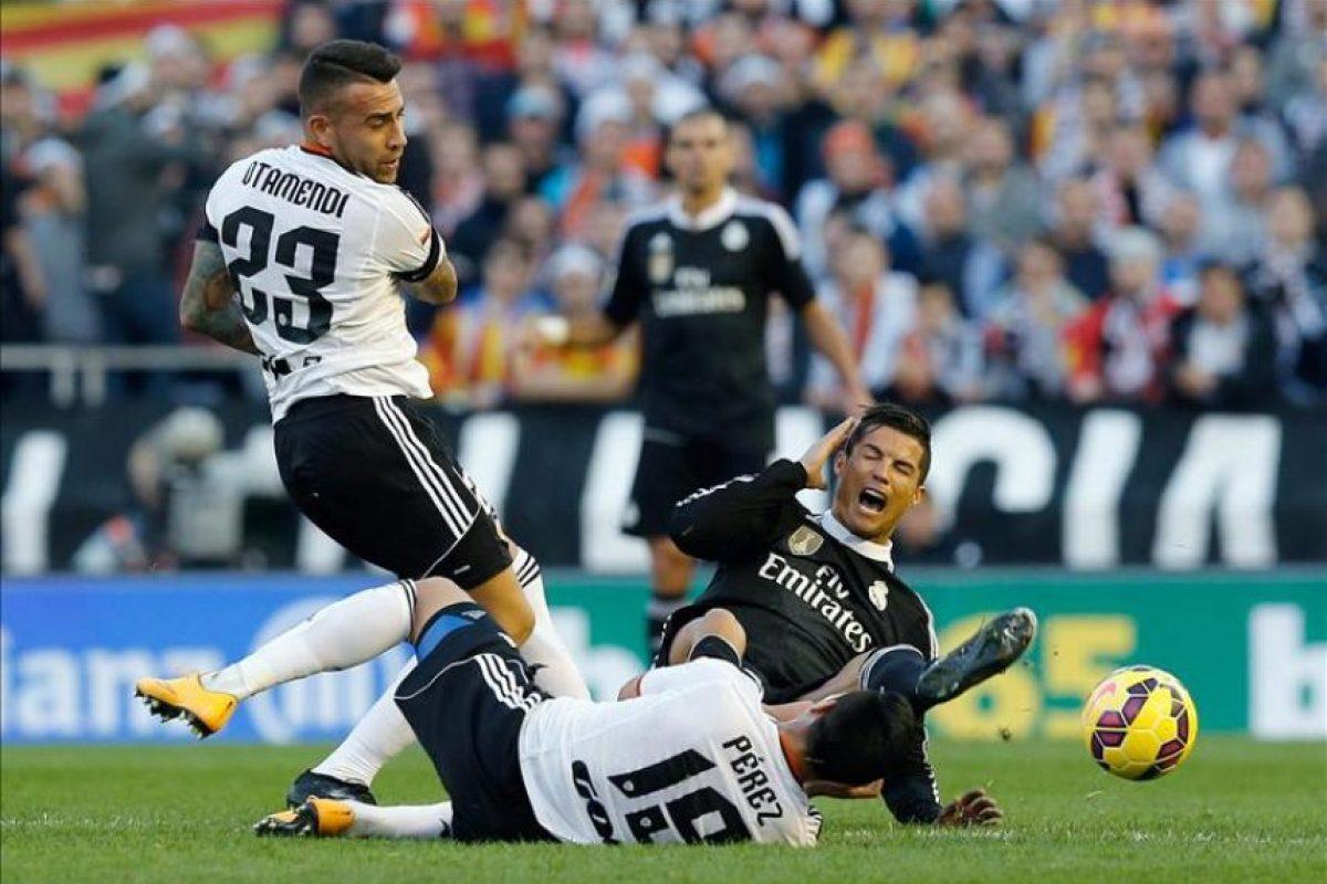El delantero portugués del Real Madrid Cristiano Ronaldo (d) cae entre el defensa argentino Nicolás Otamendi (i) y el centrocampista Enzo Pérez (c), del Valencia, durante el partido de la decimoséptima jornada de Liga de Primera División que se jugó en el estadio de Mestalla. EFE