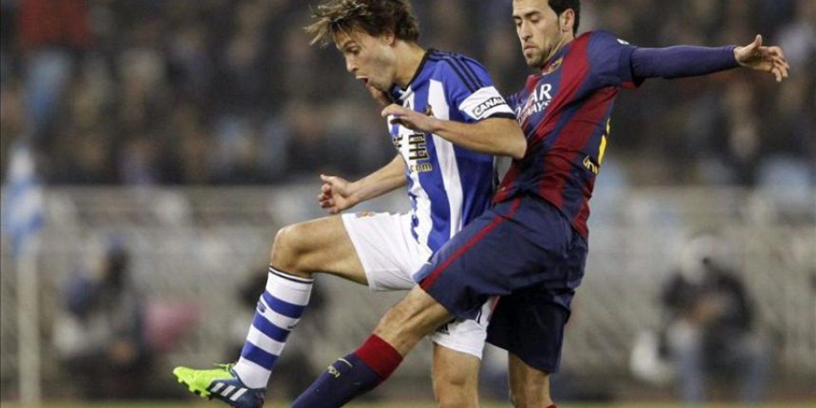 El centrocampista de la Real Sociedad Sergio Canales (i) lucha un balón con el centrocampista del FC Barcelona Sergio Busquets durante el partido de la decimo séptima jornada de Liga de Primera División disputado en el estadio de Anoeta de San Sebastián. EFE
