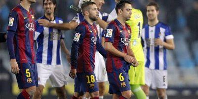 Los jugadoers del FC Barcelona, Sergio Busquets (i), Jordi Alba (c) y Xavi Hernández, se retiran del campo tras perder ante la Real Sociedad en el partido de la décimo séptima jornada de Liga de Primera División disputado en el estadio de Anoeta de San Sebastián. EFE