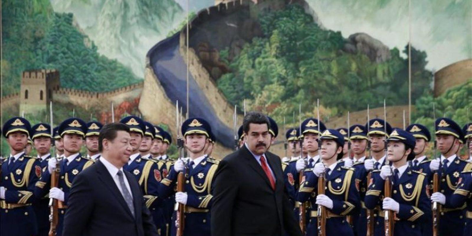 El presidente chino, Xi Jinping (izq), y su homólogo venezolano, Nicolás Maduro (dcha), pasan revista a la guardia de honor durante la ceremonia de bienvenida en el Gran Palacio del Pueblo de Pekín (China) hoy. EFE