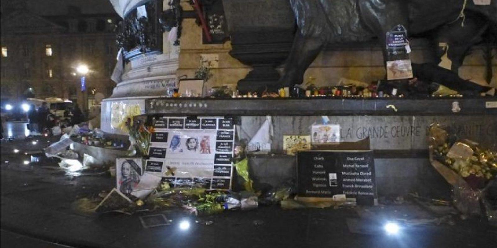 Imagen tomada anoche en la Plaza de la República de París, en el que se puede apreciar el retrato de Voltaire con una banda negra en señal de luto, junto un cartel con los nombres de las 17 víctimas de los atentados que la semana pasada conmocionaron Francia. EFE