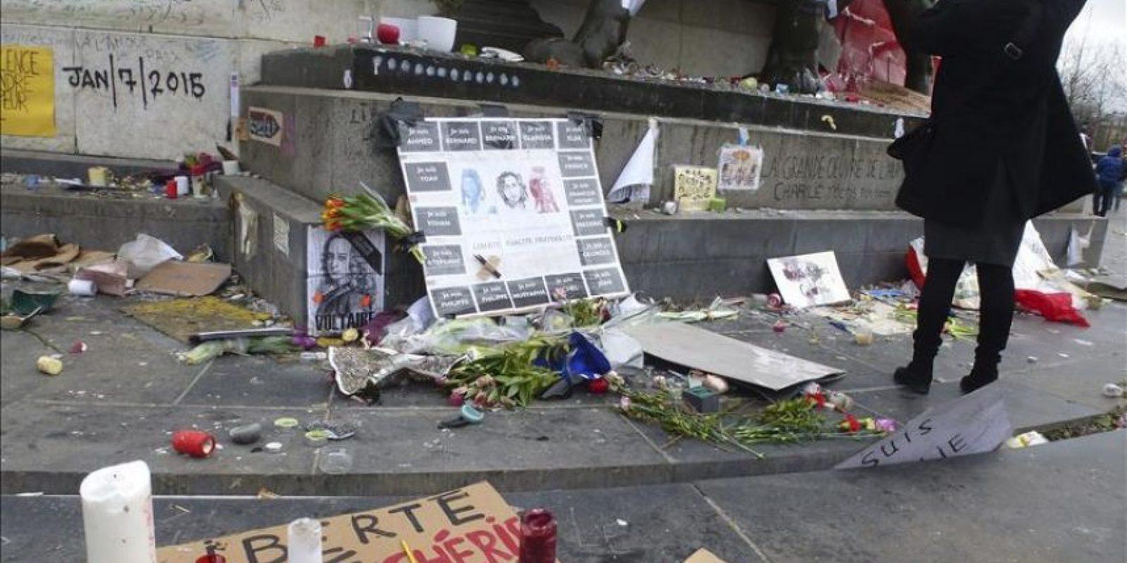Vista del retrato de Voltaire con una banda negra en señal de luto, junto un cartel con los nombres de las 17 víctimas de los atentados que la semana pasada conmocionaron Francia, hoy en la Plaza de la República de París. EFE