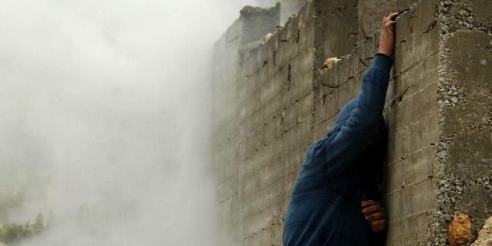 Un joven palestino se pone a cubierto junto a un muro de los botes de gases lacrimógenos lanzados por el ejército israelí durante los enfrentamientos registrados entre palestinos y soldados israelíes en el asentamiento judío de Kedumim, cerca de la localidad cisjordana de Nablus. EFE