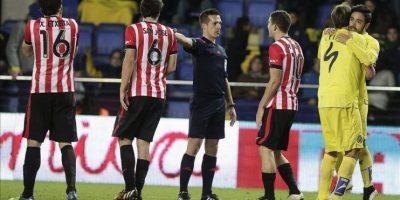 El colegiado Estrada Fernández, señala penalti ante la protesta de los jugadores del Ath. de Bilbao, durante el encuentro correspondiente a la jornada diecinueve de primera división, que han disputado frente al Villarreal en el estadio Madrigal. EFE