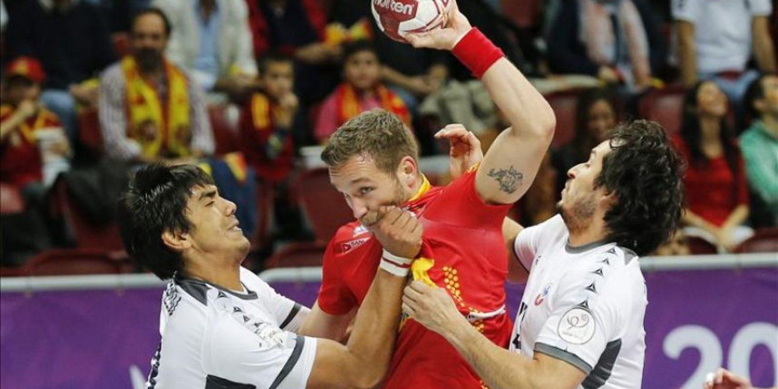 El jugador de la selección española de balonmano Víctor Tomás (c), lucha por el balón con los chilenos Guillermo Araya (d) y Javier Frelijj, durante el partido del Grupo A entre España y Chile del Mundial de Balonmano de Catar en Doha, Catar. EFE