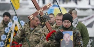 Bohdana (d), hija del voluntario del batallón Aidar, Serhiy Nikonenko, que perdió la vida en el conflicto del este de Ucrania, sostiene una foto de su padre durante su funeral en la plaza de la Independencia de Kiev, Ucrania, hoy, 20 de enero de 2015. EFE