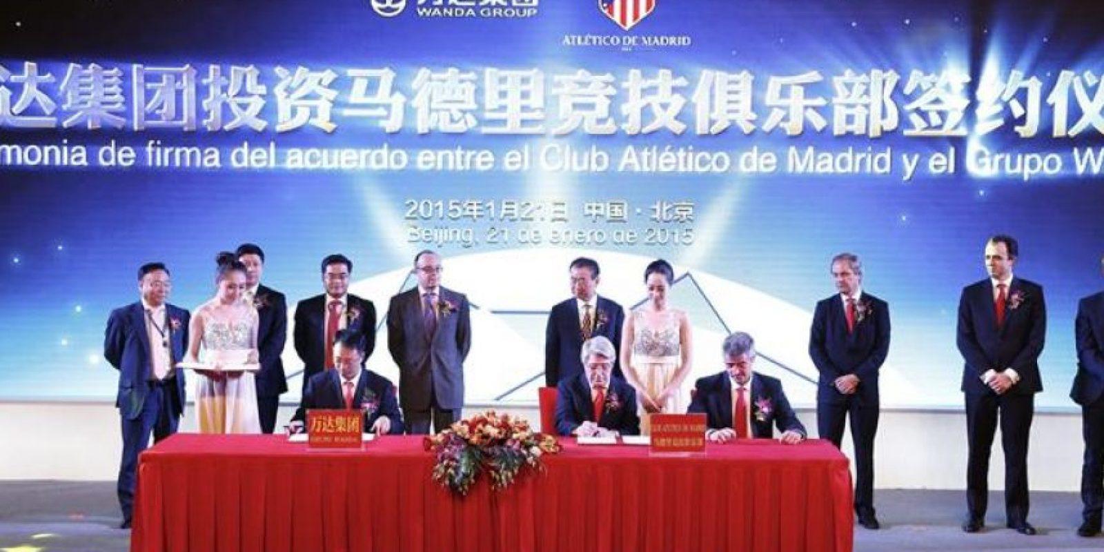El presidente de la filial cultural del grupo Wanda, Zhang Lin (izda, sentado), el presidente del Atlético de Madrid, Enrique Cerezo (centro, sentado), y el consejero delegado del club rojiblanco, Miguel Ángel Gil (dcha, sentado), firman un acuerdo ante el magnate y propietario del gigantesco conglomerado empresarial Wanda, Wang Jianlin (en pie, 5ºdcha), en Pekín (China) este miércoles 21 de enero de 2015. EFE