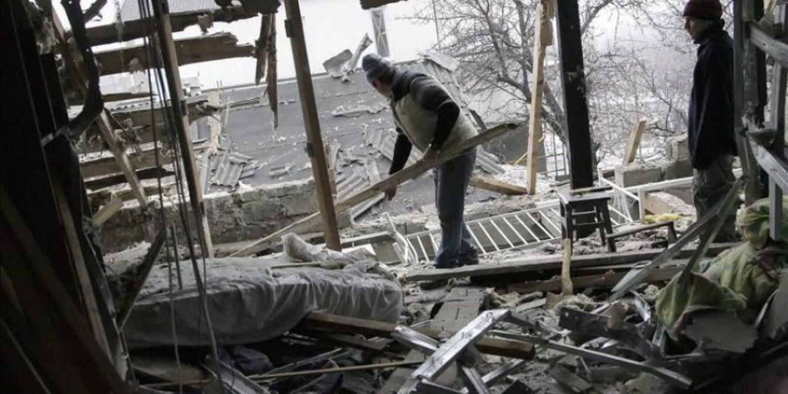 Dos hombres retiran los escombros de su casa causados por los bombardeos en Donetsk, Ucrania hoy 21 de enero de 2015. EFE