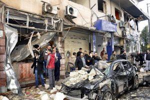 Fotografía facilitada por la Agencia Siria Árabe de Noticias (SANA) en la que se muestra a varios policías y ciudadanos sirios alrededor de los escombros provocados por la explosión de un coche bomba en el barrio de Akrama, en el centro de Homs, Siria, hoy, miércoles 21 de enero de 2015. EFE