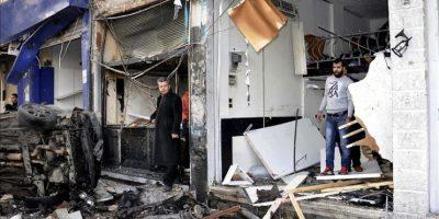 Fotografía facilitada por la Agencia Siria Árabe de Noticias (SANA) en la que se muestra a varios ciudadanos sirios alrededor de los escombros provocados por la explosión de un coche bomba en el barrio de Akrama, en el centro de Homs, Siria, hoy, miércoles 21 de enero de 2015. EFE