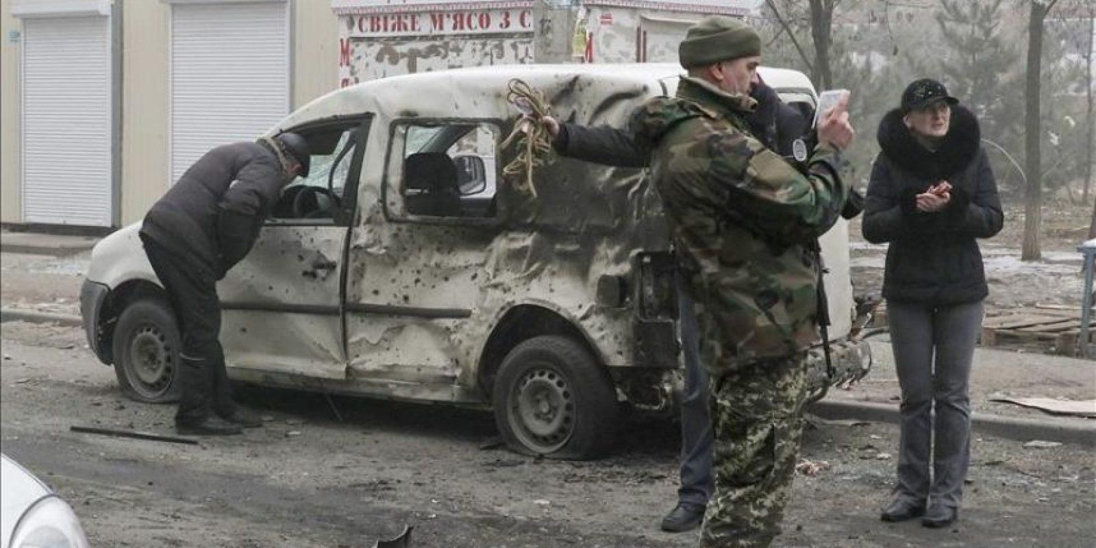 Militares ucranianos inspeccionan un coche dañado después de un bombardeo en la ciudad de Mariupol, en el este del país. EFE