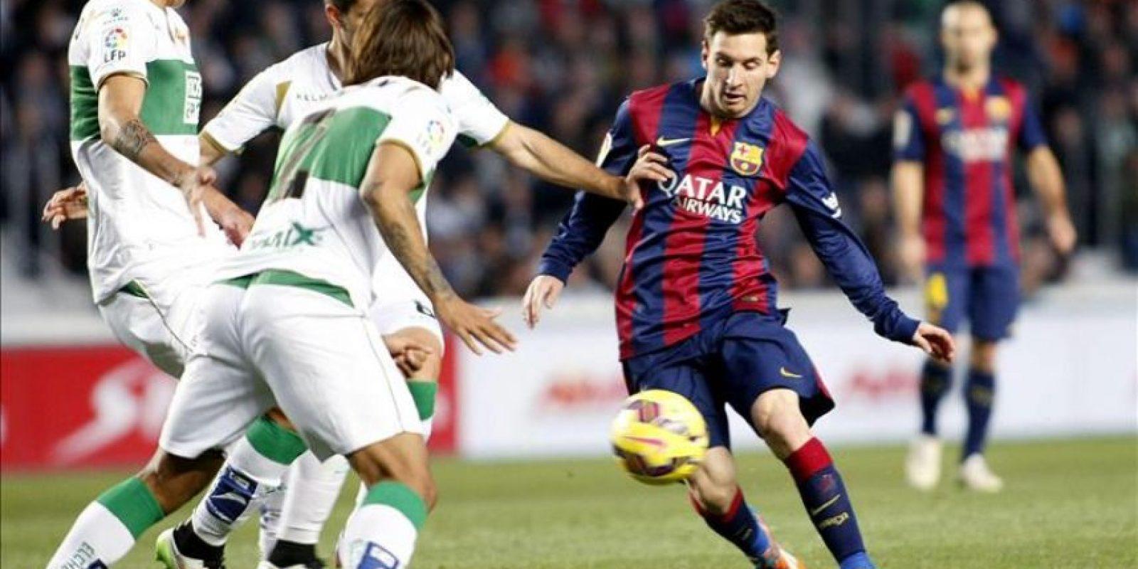 El delantero argentino del FC Barcelona Lionel Messi (d) ante tres defensores del Elche, durante el partido de la vigésima jornada de liga en Primera División que se disputó en el estadio Martínez Valero. EFE