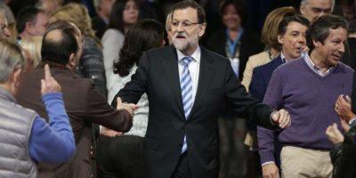 El presidente del Gobierno, Mariano Rajoy (c), junto al vicesecretario de Organización y director de campaña del PP, Carlos Floriano (d), saluda a los militantes, a su llegada hoy a la clausura de la convención nacional del PP, que se ha celebrado este fin de semana en el Palacio de Congresos de Madrid. EFE