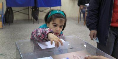 Una niña deposita el voto de su padre en una urna, en un colegio electoral de Atenas. EFE
