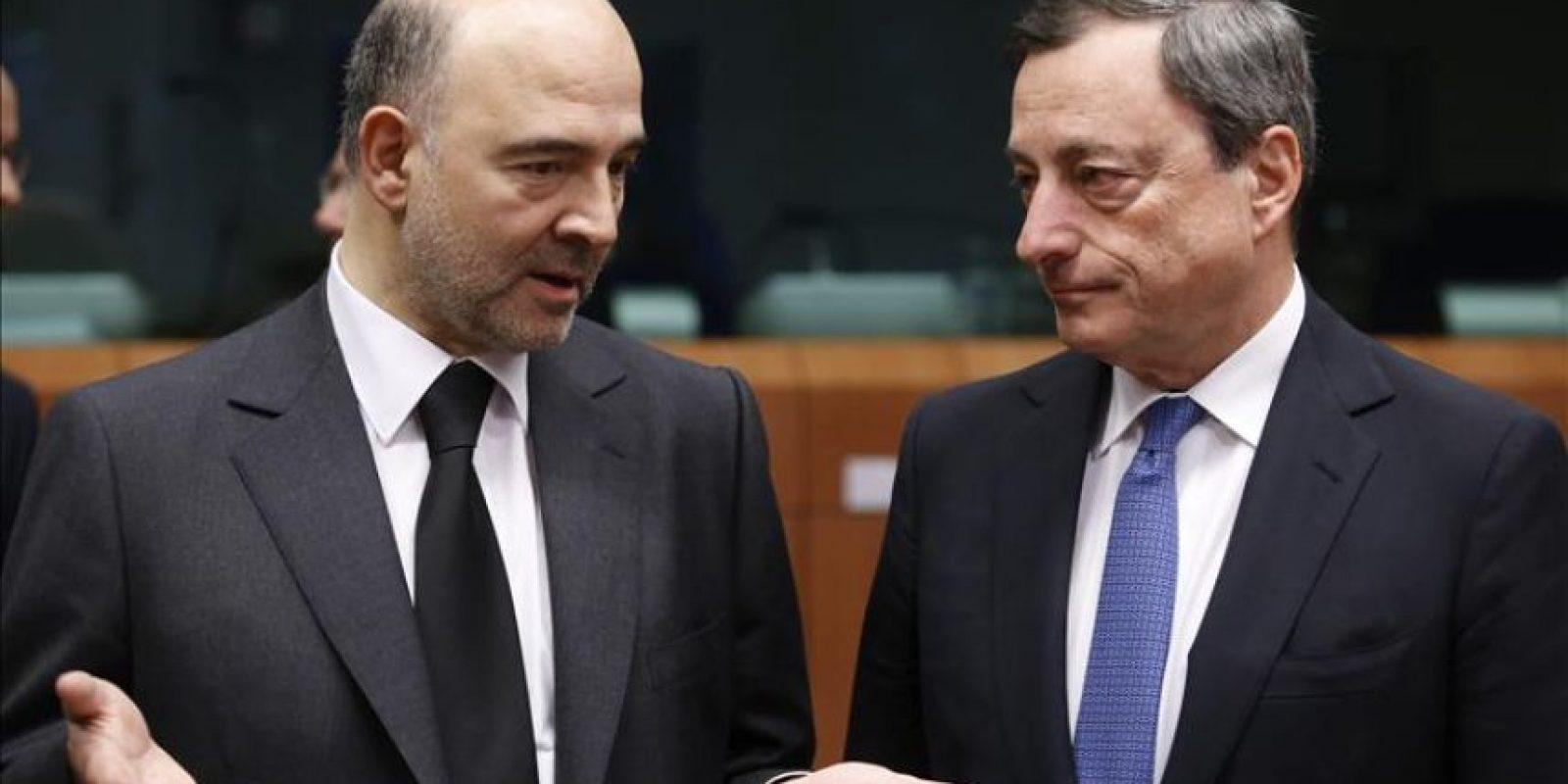 El comisario europeo de Asuntos Económicos, Pierre Moscovici (i), habla con el presidente del Banco Central Europeo, Mario Draghi (d), al inicio de la reunión de los ministros de Economía y Finanzas de la eurozona (Eurogrupo) en Bruselas, Bélgica. EFE