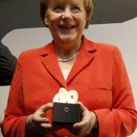La canciller alemana Angela Merkel sostiene una escultura diseñada por un niño de 11 años de edad Foto:Getty Images