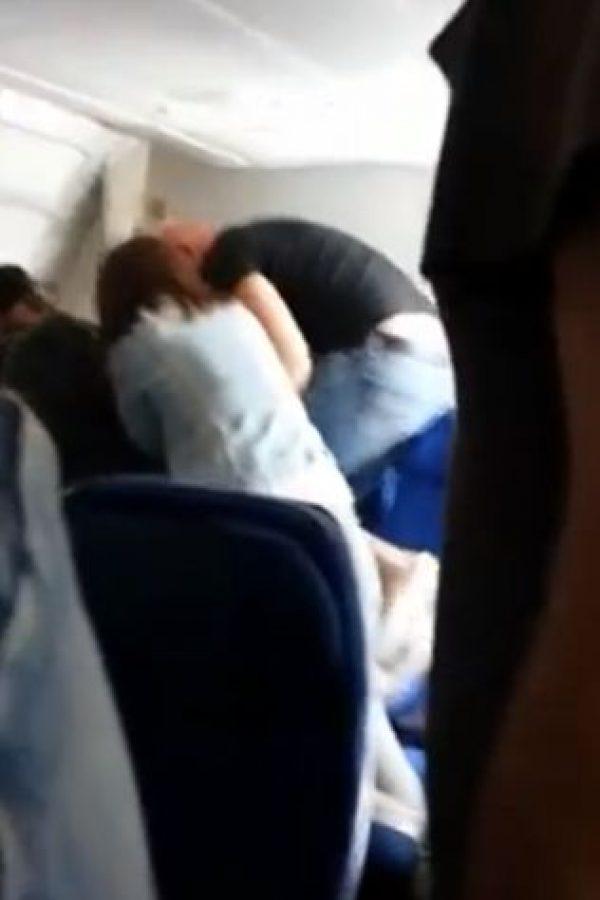 Una de las policías golpea al pasajero y le dice a la tripulación que este no puede seguir grabando.