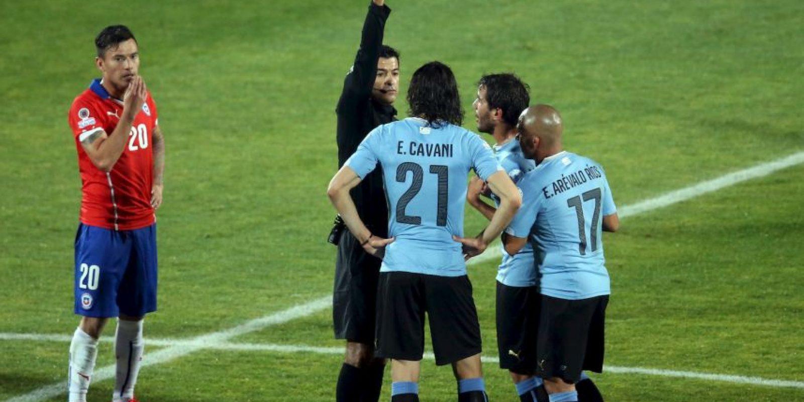 El réferi vio la bofetada que dio el delantero charrúa a Gonzalo Jara, pero no se percató que el chileno tocó el trasero del ariete Foto:AFP