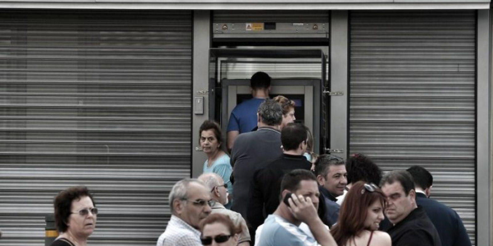 Largas filas para poder utilizar los cajeros automáticos, los cuales solamente dan máximo 60 euros al día por tarjeta Foto:AFP