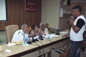 En esas imágenes se ve al expresidente de Cuba vestido con chaqueta blanca deportiva y camisa de cuadros, sentado en la mesa de cabecera de una sala de reuniones acompañado de dos funcionarias cubanas. Foto: Granma.cu