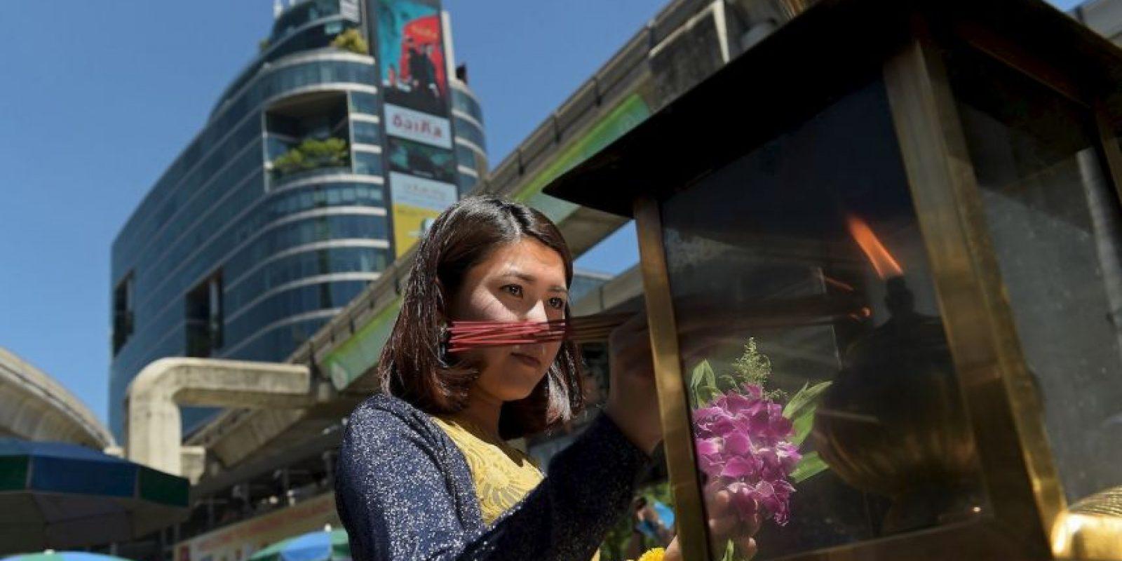 Mujer enciende inciensos en Tailandia. Foto:AFP