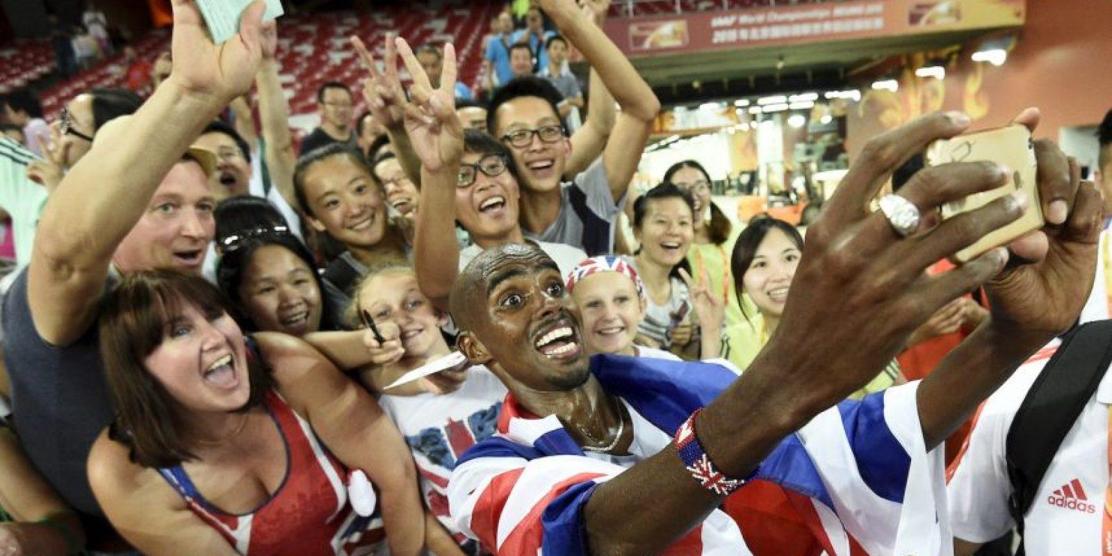 Mo Fa posa con fanáticos al ganar la final de 10 mil metros de atletismo en el Campeonato Mundial de la IAAF 2015. Foto:AFP