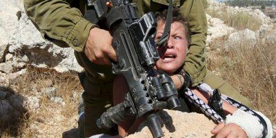 Soldado israelí controla a niño palestino. Foto:AFP