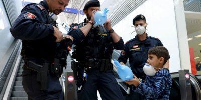 Policías australianos llenan guantes como si fueran globos para que un refugiado sirio juegue. Foto:AFP