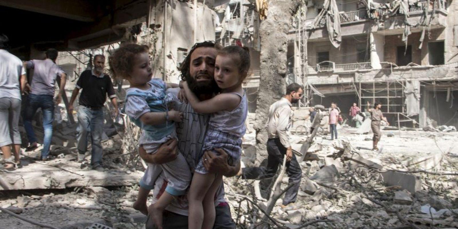 Hombre trata de salvar a dos niñas tras detonaciones de bomba en Siria. Foto:AFP