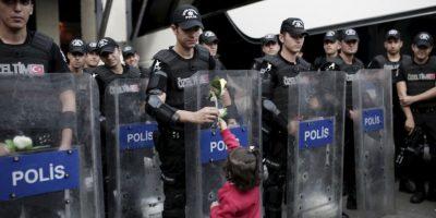 Niña migrante le regala una flor a un policía antidisturbios turco. Foto:AFP
