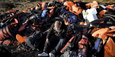 Hombre sentado en una pila de salvavidas en la isla de Lesbos, en Grecia. El pasado 27 de septiembre se ahogaron 17 sirios tratando de llegar al lugar. Foto:AFP