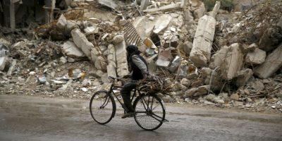 Hombre pasa en su bicicleta por una zona destruida por el conflicto en Siria. Foto:AFP