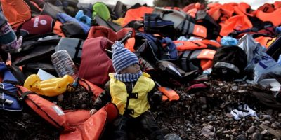 Niño refugiado sentado sobre una pila de chalecos salvavidas en la isla Lesbos. Foto:AFP