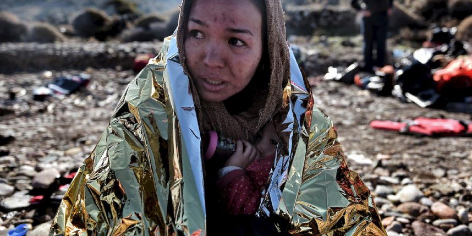 Refugiada protege a su hijo en una manta termanl a su llegada a Lesbos. Foto:AFP