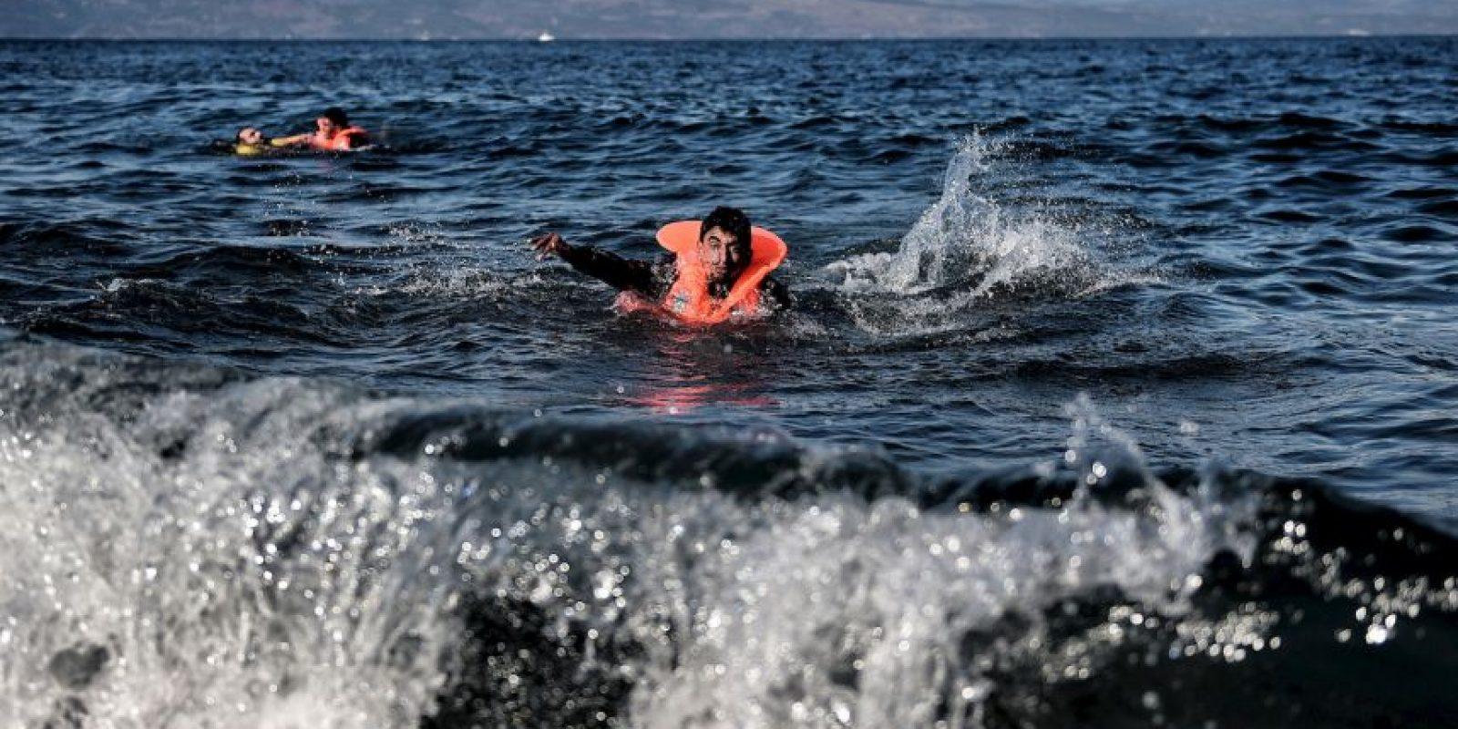 Dos hombres migrantes nadan hacia la costa de la isla Lesbos. Foto:AFP