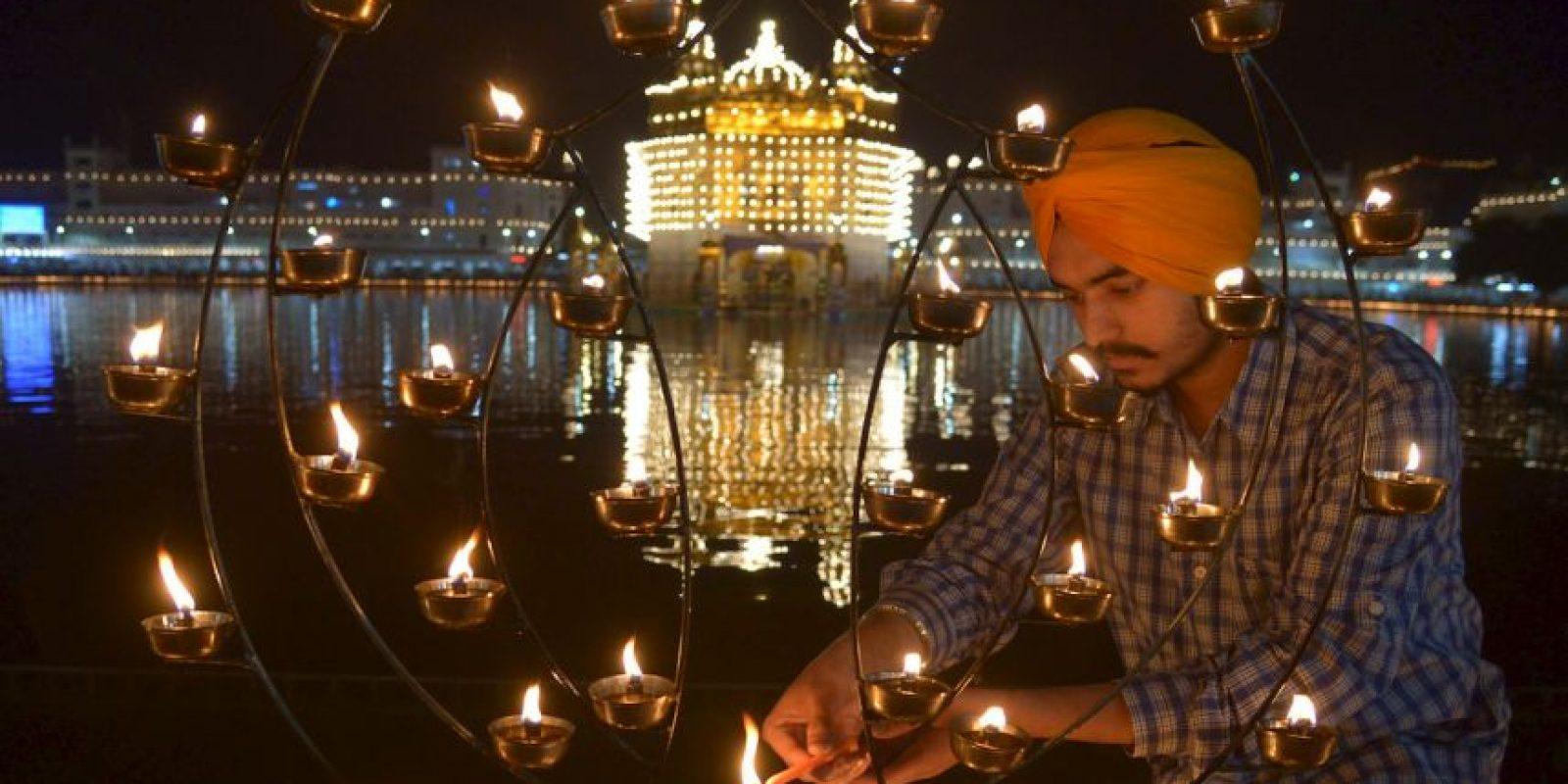 Devoto indio enciende velas prestando respetos en el Templo Dorado de Amritsar. Foto:AFP